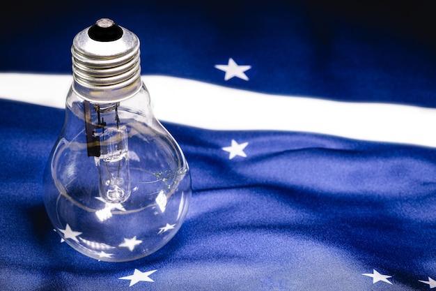 ブラジルの国旗のテクスチャ、エネルギー危機とブラジルの停電の概念上のひび割れて焼けたヴィンテージ電球