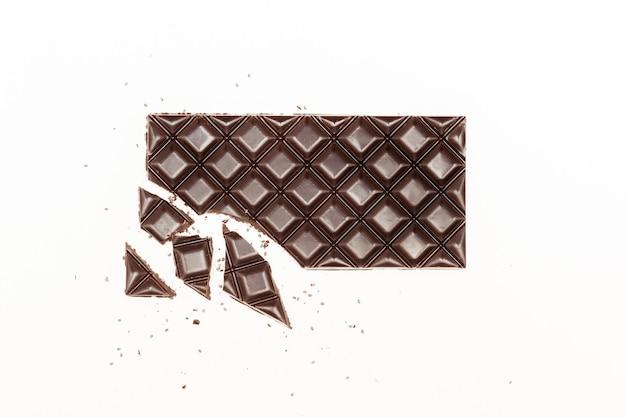Треснувший шоколадный батончик с семенами чиа на белой стене