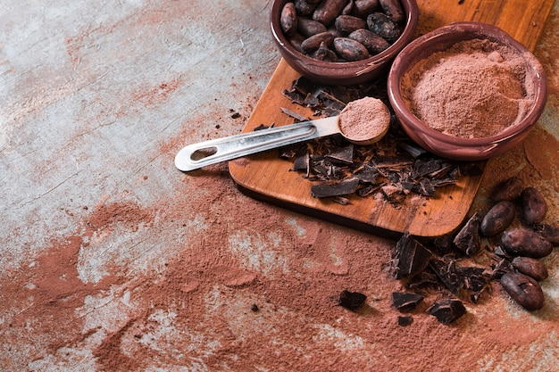 Cracked chocolate bar with cocoa powder and beans