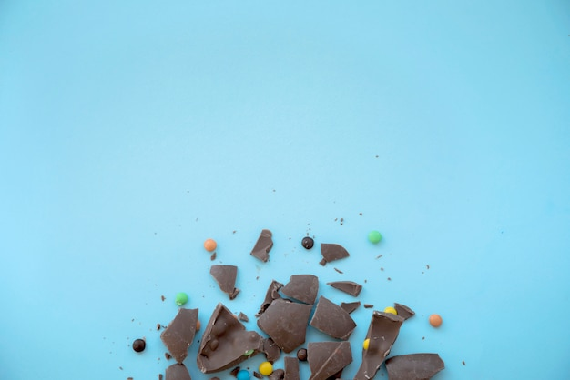 Cracked chocolate with candies on blue table