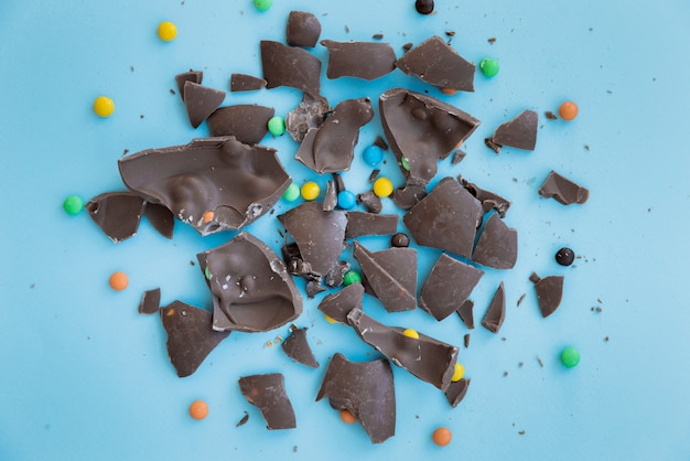 Cracked chocolate with candies on table