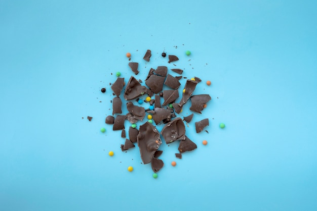 Cracked chocolate with small candies on blue table