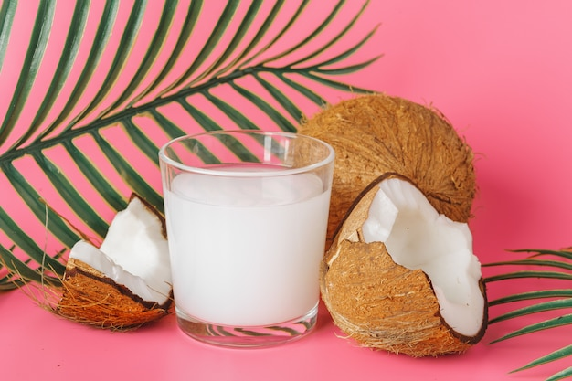 Cracked coco and coconut milk in glass on bright pink background