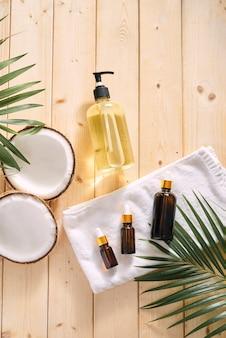 금이 간 코코넛과 테이블에 오일 한 병 - 스파, 스킨케어, 헤어케어, 휴식 개념