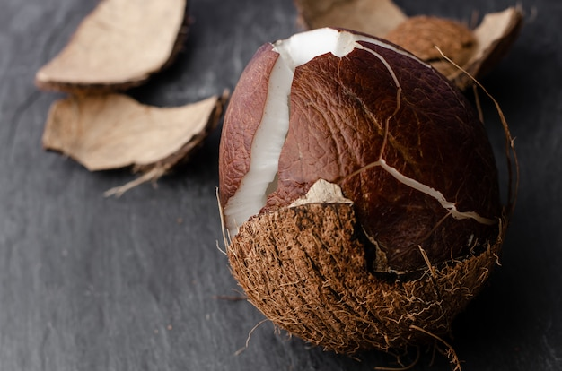 Cracked coconut on dark stone