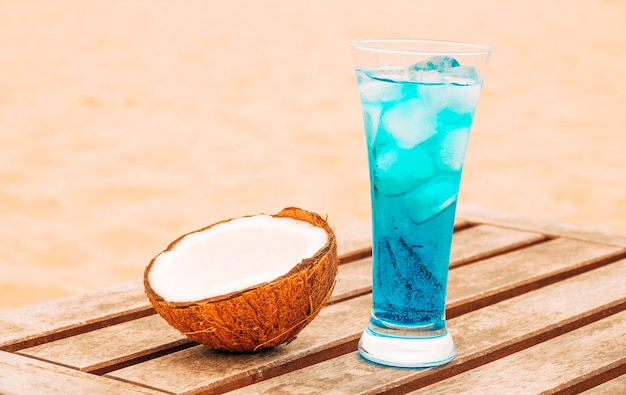Cracked coconut and glass of bright blue drink at wooden table