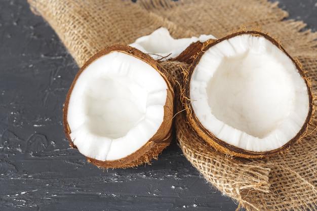 Cracked coconut pieces on dark wooden background