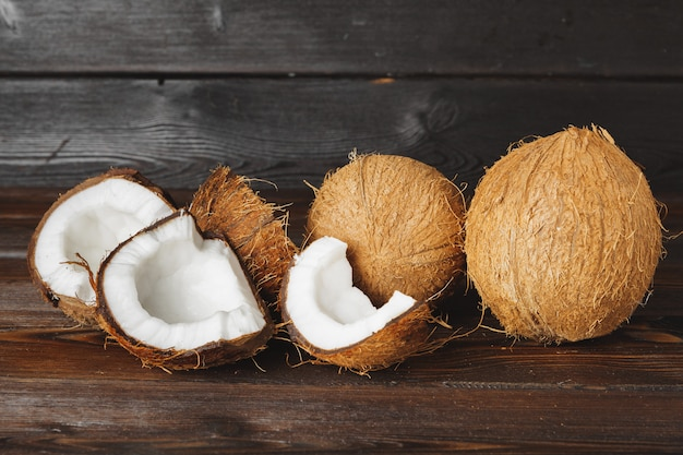 Cracked coconut pieces on dark wooden surface
