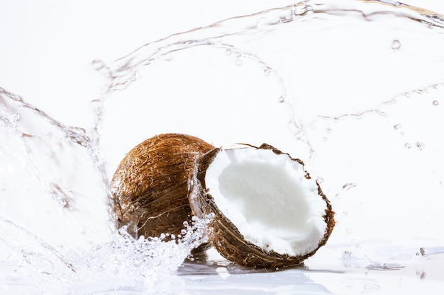 Cracked coconut with water splash