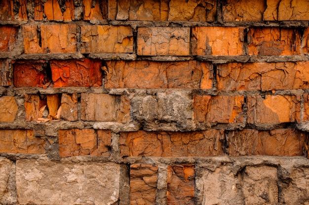 ひびの入ったコンクリートヴィンテージオレンジ、赤、ベージュのレンガ壁の背景