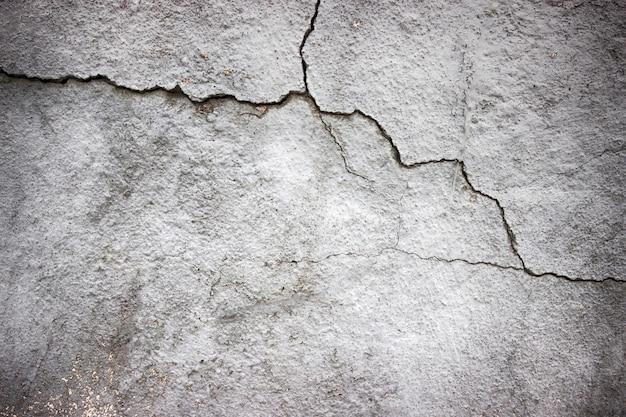 Бетонная стена с трещинами, покрытая серой текстурой цемента