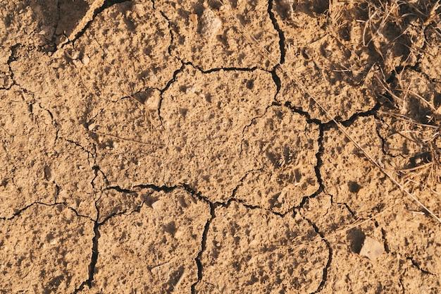 ひび割れた乾燥地。き裂を有する茶色の背景