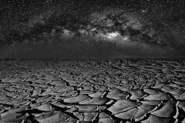 Cracked dry land and universe space of milky way galaxy on night sky.