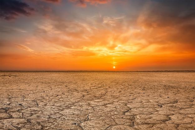 ひび割れた大地土壌の日没の風景