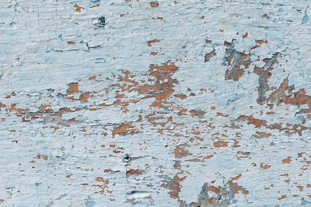 古い石の壁にひびの入ったフレーキング白いペンキ