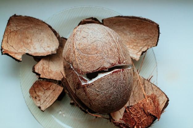 テーブルの上のひびの入った新鮮なココナッツ熟したフルーツナッツココナッツの殻健康的なライフスタイルの楽園のコンセプト