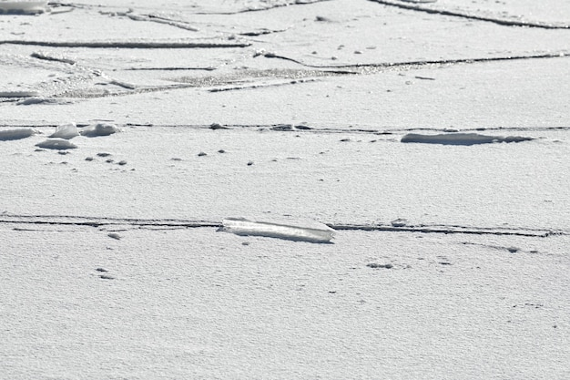 Cracked ice of frozen lake with white snow on top. ice texture background, close up.