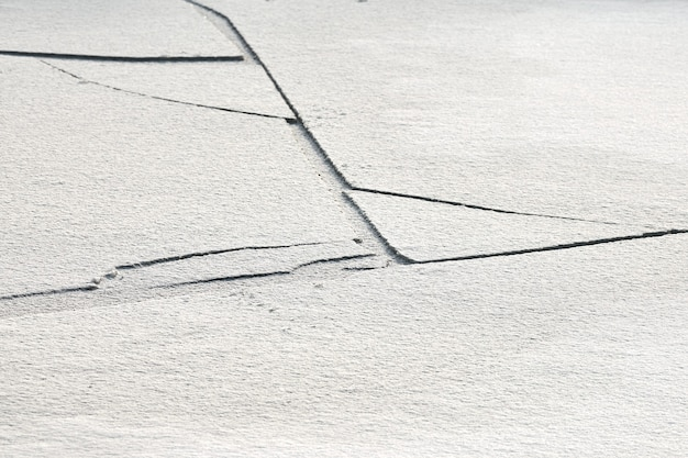 Cracked ice of frozen lake with white snow on top