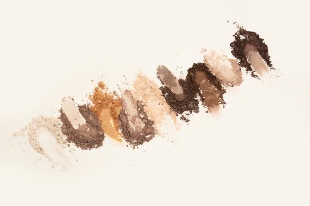 Треснувший набор теней для век в основных коричневых тонах на сером фоне