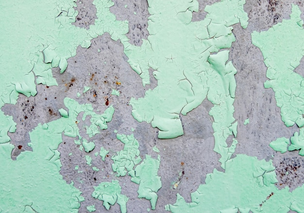 Cracked and peeling of green color paint on steel with rusted texture and background