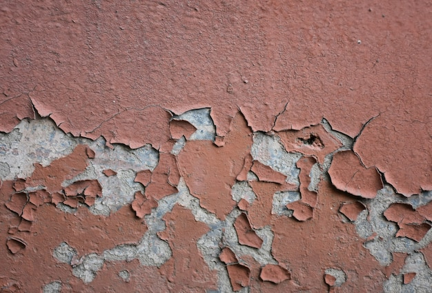 Cracked peeling plaster on the wall background