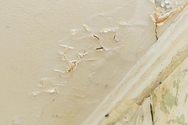 Потрескавшаяся штукатурка на потолке после протечки воды с верхнего этажа в жилом доме