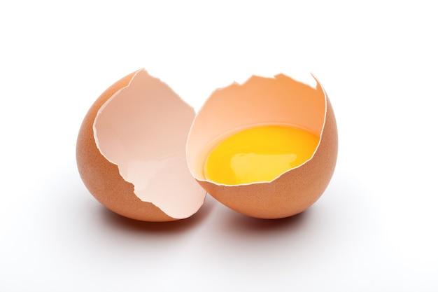 ひびの入った生の茶色の卵、白いスペースの卵殻の卵黄
