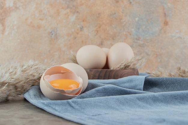 Треснувшее сырое яйцо на мраморной поверхности тканью
