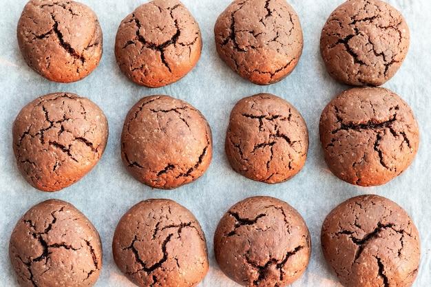 Треснувшее круглое шоколадное печенье на противне с пергаментной бумагой
