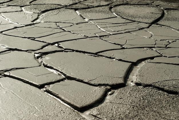 Треснувшая мокрая глина на дне сухого пруда в засушливой местности