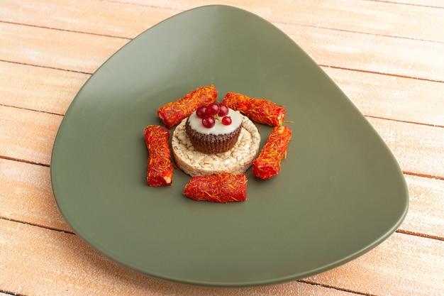 クラッカーとクリームのヌガーとチョコレートケーキとグリーンプレート内のケーキ
