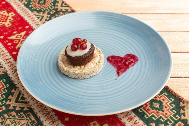 Крекер и пирог с клюквой сверху внутри синей тарелки на сливках