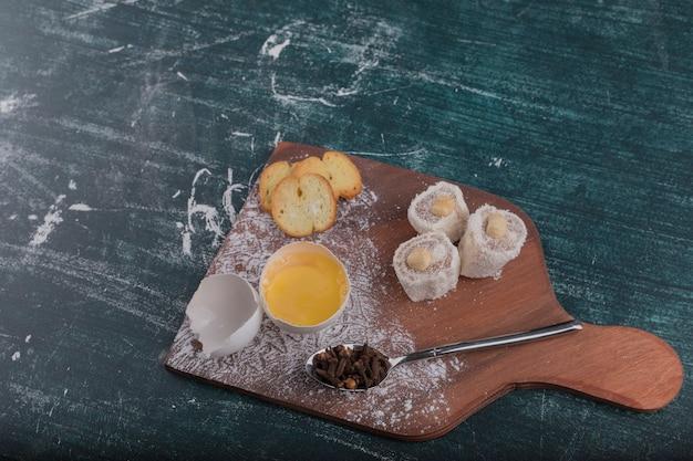 Сухарики и лакомства с яичным желтком на деревянной доске
