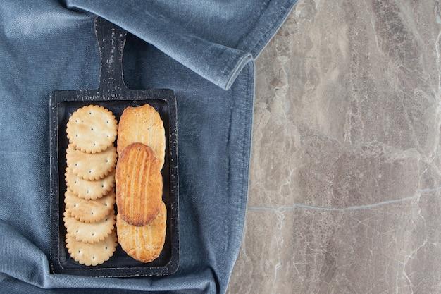 Крекер и песочное печенье, доска на полотенце, на мраморе.
