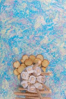 Сухарики и вафельные палочки с лукумом в стеклянной тарелке