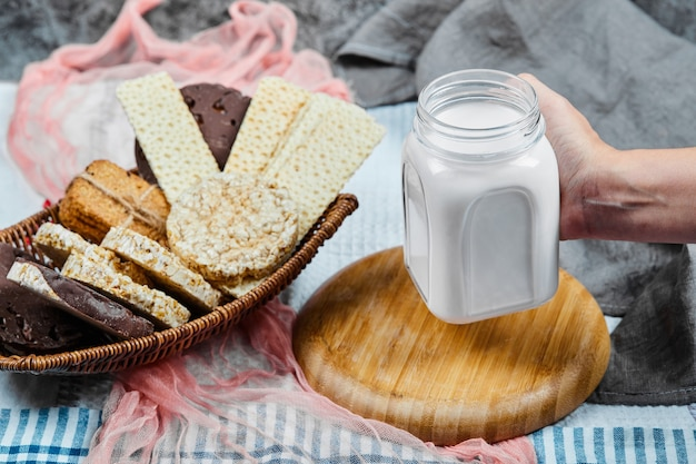 Cracker and cookies with a jar of milk.