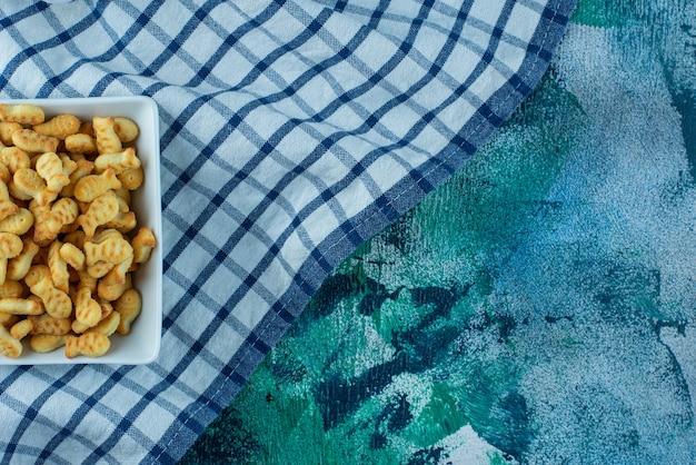 Pesce cracker in una ciotola su un canovaccio, sul tavolo blu.