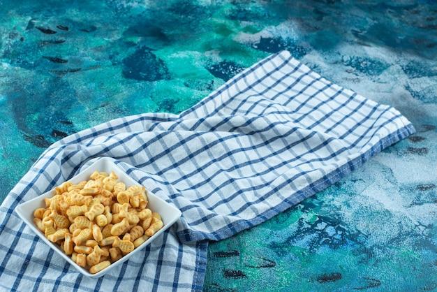 Рыба крекера в миске на кухонном полотенце, на синем столе.
