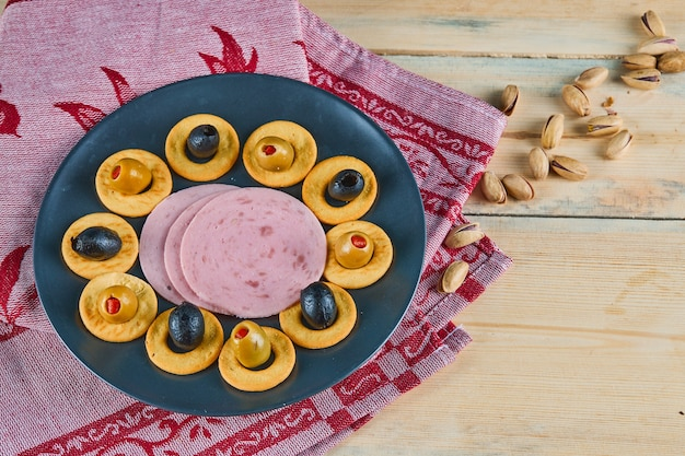 ピンクのテーブルクロスをかけたセラミックプレートに、クラッカーリングとオリーブとソーセージのスライス。