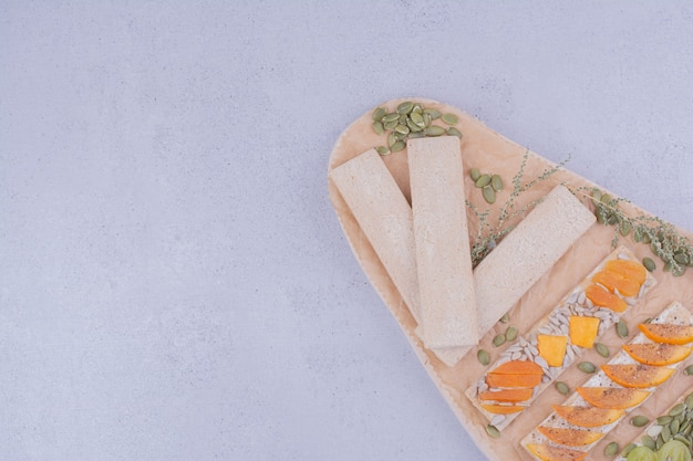 Cracker sandwiches with herbs and fruits on a wooden board