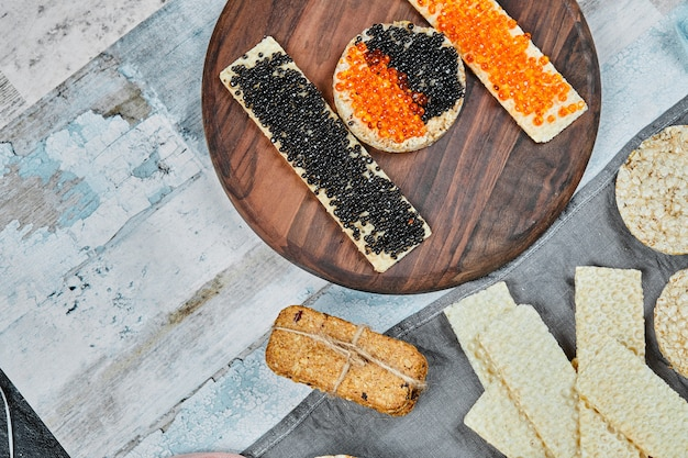 빨간색과 검은 색 캐비어와 크래커 샌드위치.