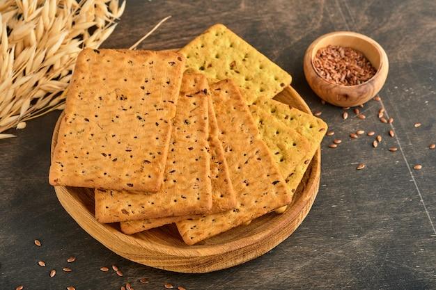 暗い木製のテーブルに亜麻仁とオートブランの長方形の形をしたクラッカー。適切な栄養のためのスナック。
