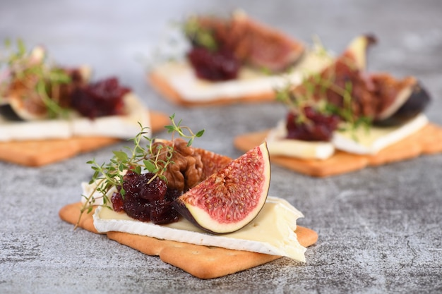 Cracker with a slice of camembert jam figs and nuts a great snack idea for a holiday