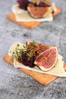 Cracker with a slice of camembert jam figs and nuts
