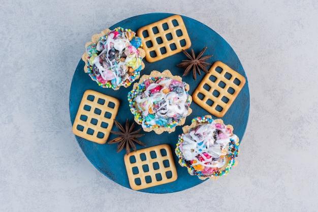 大理石のテーブルの上のボード上のクラッカーとキャンディーカップケーキ。