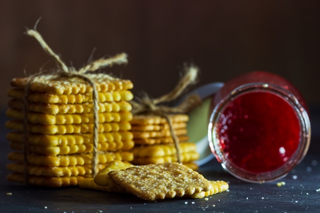 Crackers are tied with hemp rope and strawberry jam bottle on table in dark