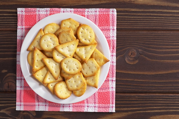나무 테이블에 있는 접시에 치즈 맛이 나는 크래커 비스킷, 위쪽
