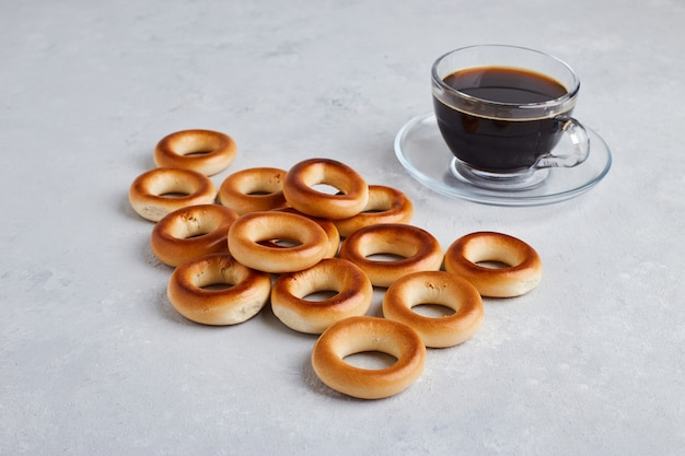 Crackers and buns isolated on white surface with a cup of coffee.