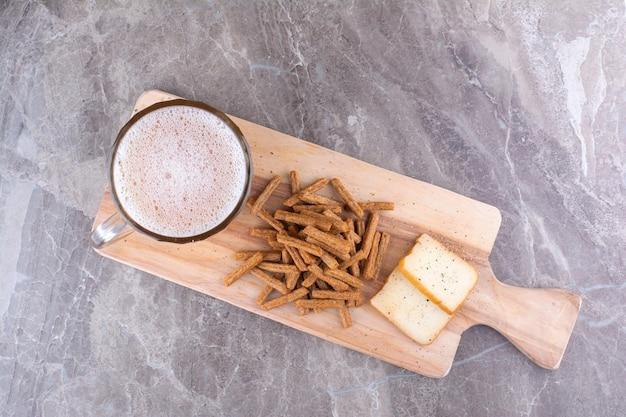 Крекеры, сыр и стакан пива на деревянной доске. фото высокого качества