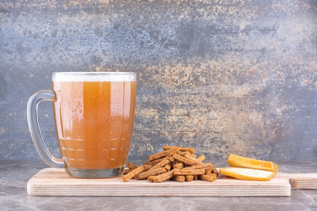 Crackers, cheese and glass of beer on wooden board. high quality photo
